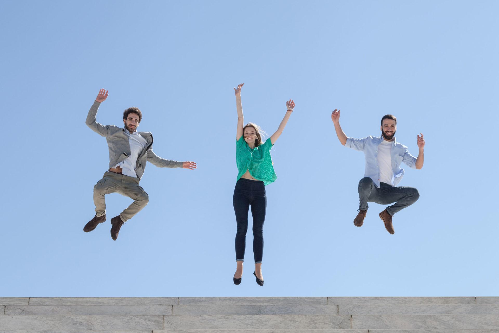 Spaß am Lernen und Erfolg wird durch springende Menschen, die Lebensfreude versprühen, dargestellt.